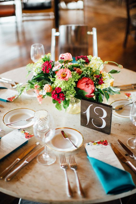 a super colorful centerpiece with red peonies, pink and green blooms and greenery