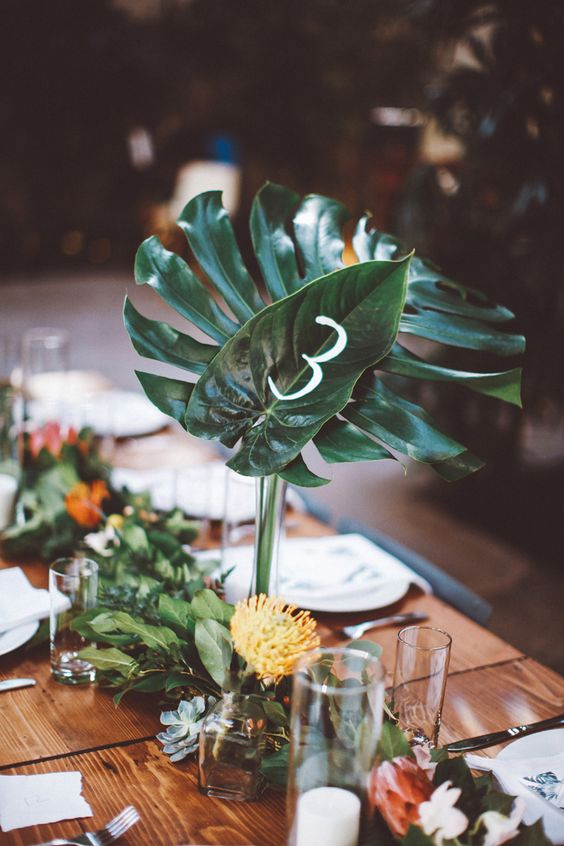 a tropical runner of various greenery, succulents and white blooms and pincushion proteas
