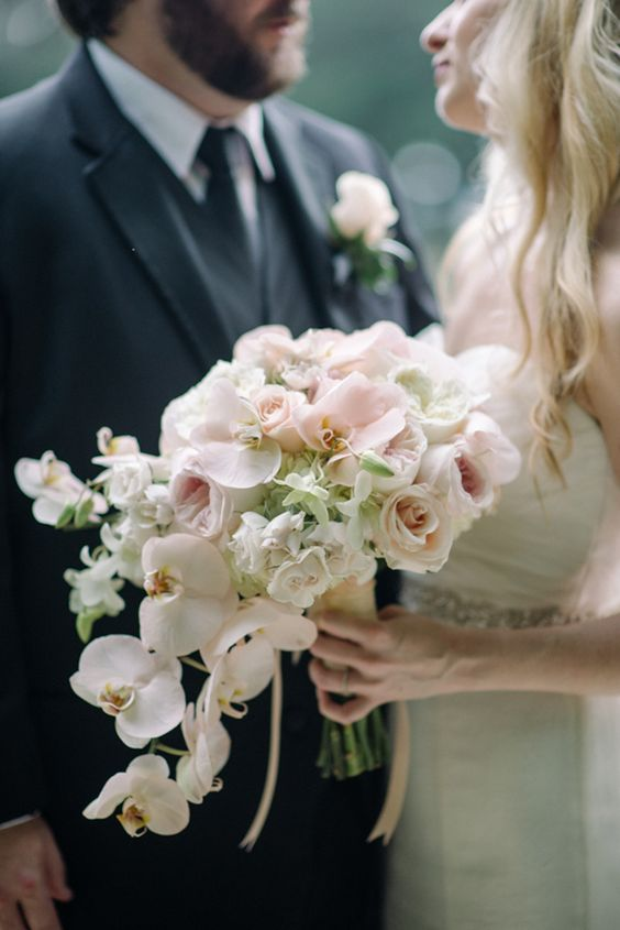 blush roses and peonies and white orchids for a beautiful cascading bouquet