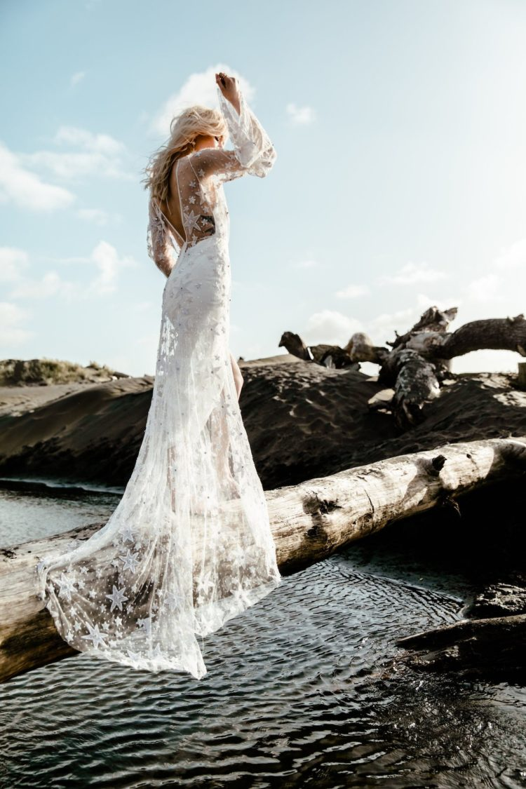 Indigo Star wedding dress with a high low slip dress and a sheer overdress with star appliques, a train and long sleeves