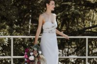 02 One of the brides was wearing a strapless sheath wedding dress with a draped bodice and statement earrings