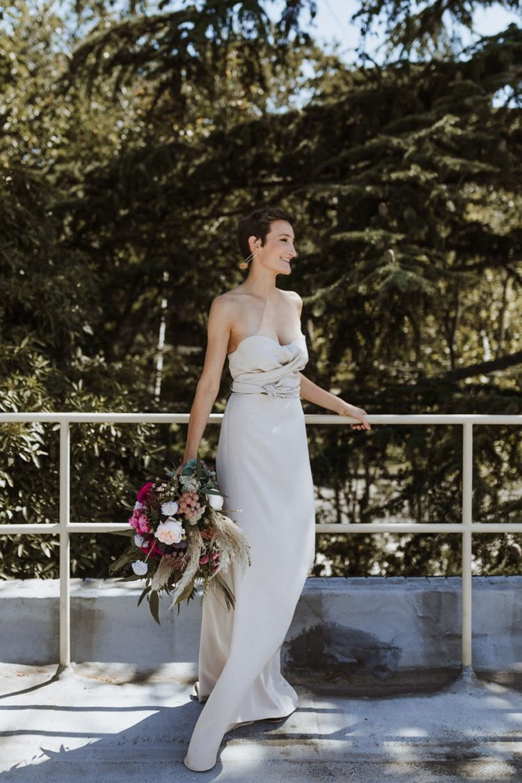 One of the brides was wearing a strapless sheath wedding dress with a draped bodice and statement earrings
