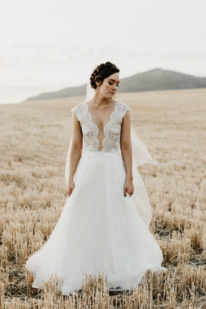 The bride was wearing a gorgeous A-line wedding dress with a lace bodice, an illusion plunging neckline, cap sleeves and a layered skirt