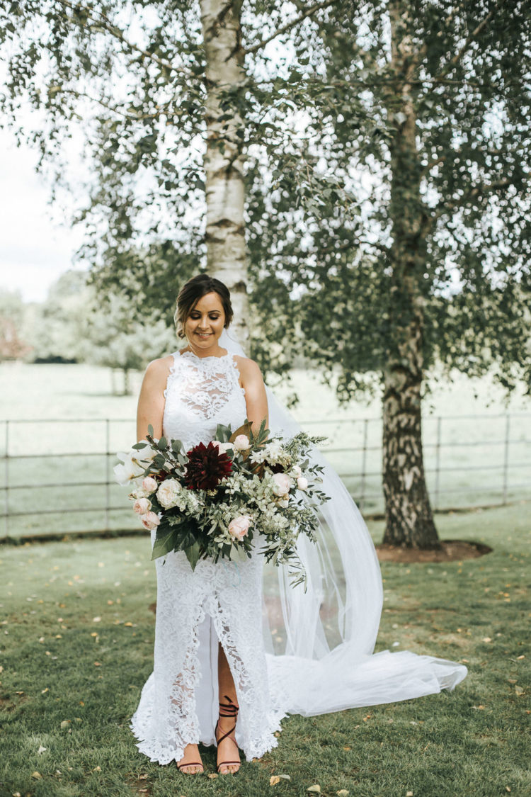 The bride was wearing a lace sheath dress with an illusion halter neckline and a front slit