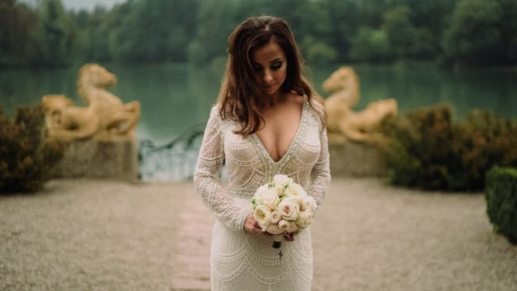 The bride was wearing an embellished sheath dress with a V-neckline, long sleeves and a train