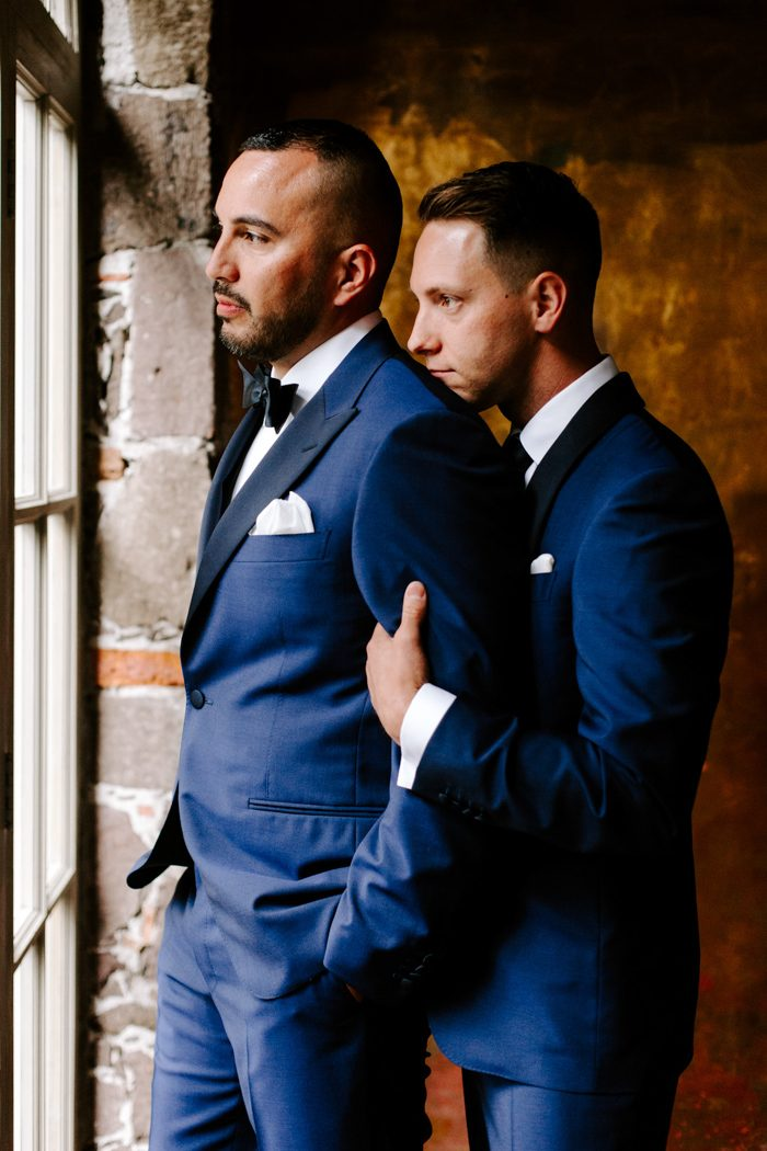 The grooms were wearing navy tuxedos with black lapels and chose different ties