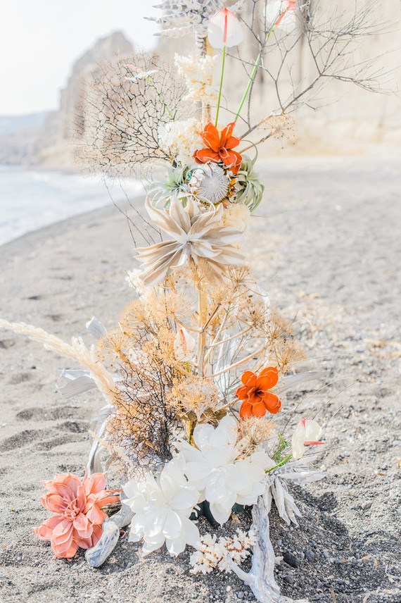The wedding arch was hand crafted of corals, large blooms and apinted succulents plus driftwood for a creative look