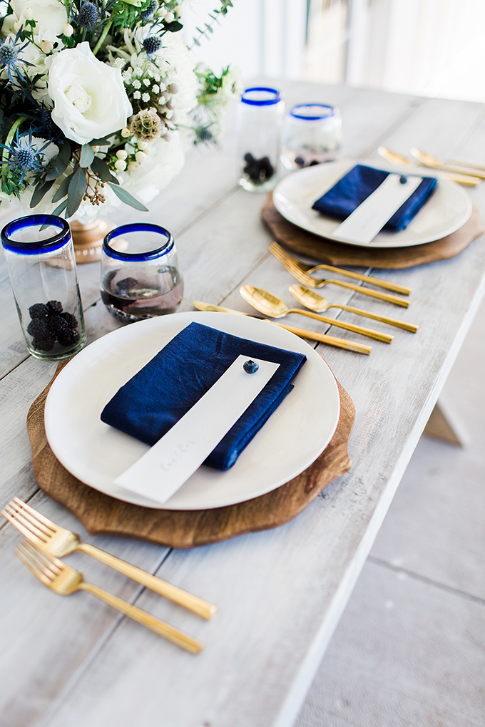 The wedding table setting was done with a whitewashed table, wooden chargers, navy napkins, sheer glasses with a blue rim and gold cutlery