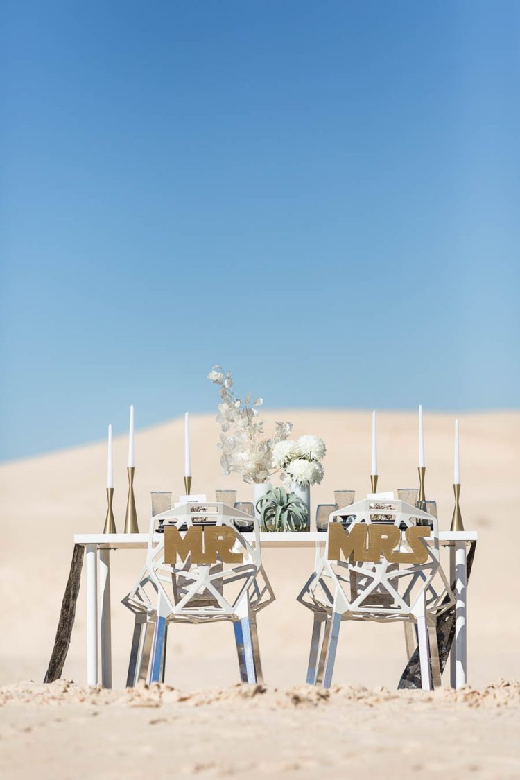 The wedding table was styled with candles, white blooms, the chairs were geometric ones with gold letters