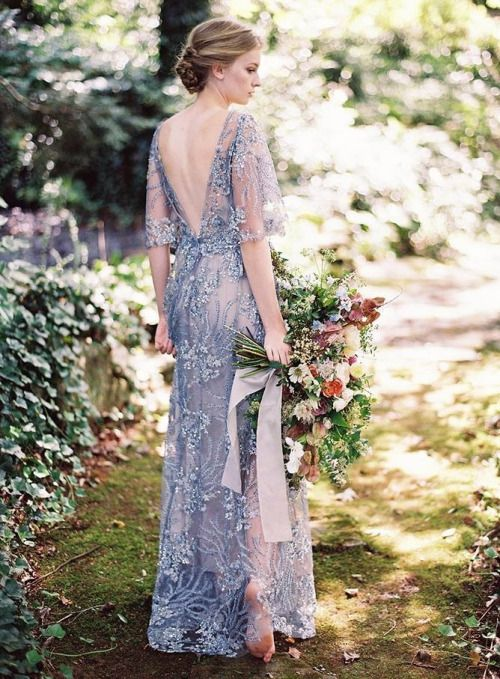 a blue lace embroidered and embellished wedding dress with bell sleeves and an open back