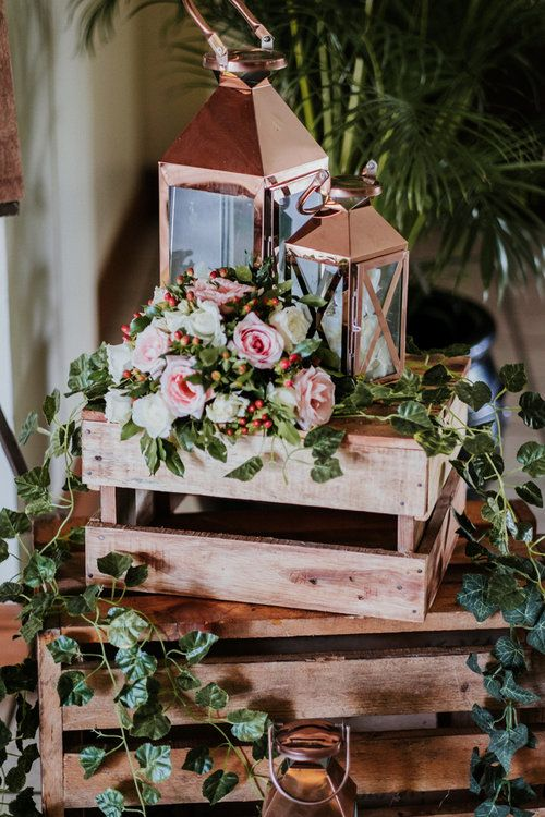 a cute rustic wedding decoration with crates, greenery, blooms and candle lanterns