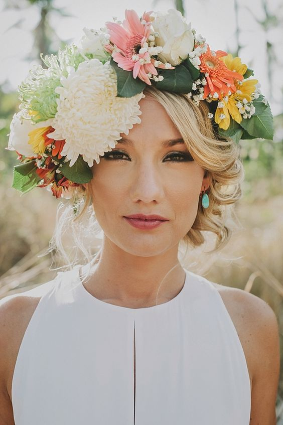 a large summer floral crown with neutral, pink, yellow and orange blooms plus greenery
