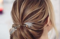 02 a low messy chignon hairstyle with a bump and much texture for a chic look plus a clear ribbon bow