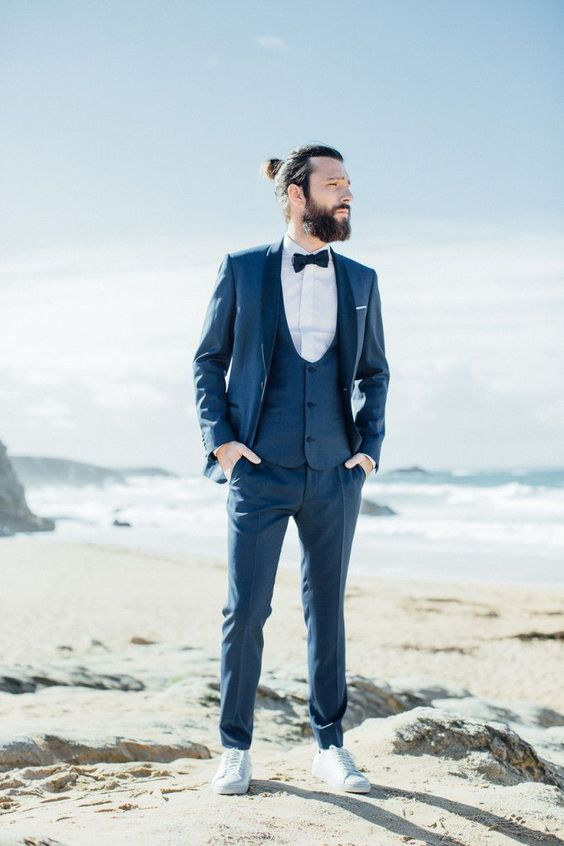 a navy htee-piece suit with a white shirt, a navy bow tie and white sneakers for a relaxed feel