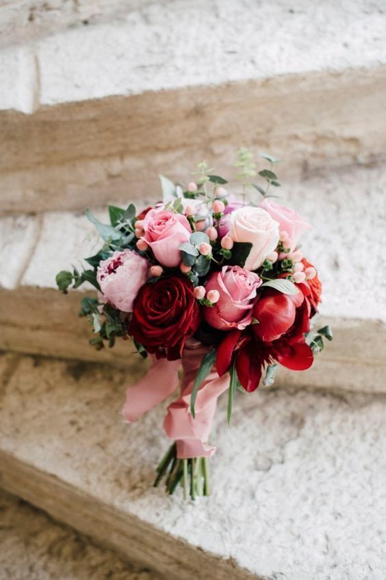 a romantic bridal bouquet of blush, pink and burgundy blooms plus a pink ribbon