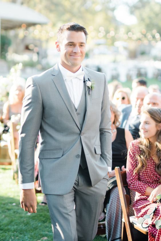 a stylish grey three-piece wedding suit in light grey, a white shirt and a white bow tie