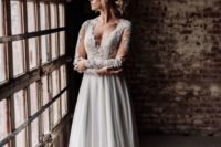 02 a wedding gown with a lace bodice with an illusion plunging neckline, long sleeves and a аlowy skirt with a train