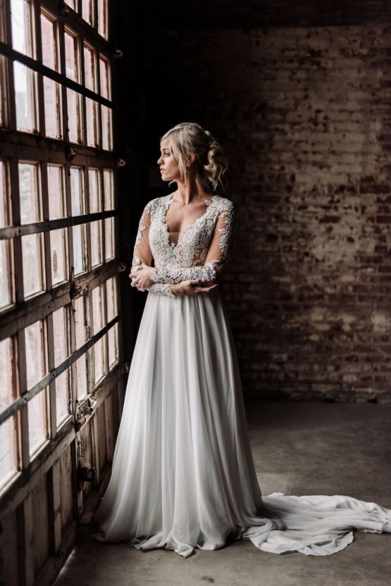a wedding gown with a lace bodice with an illusion plunging neckline, long sleeves and a аlowy skirt with a train