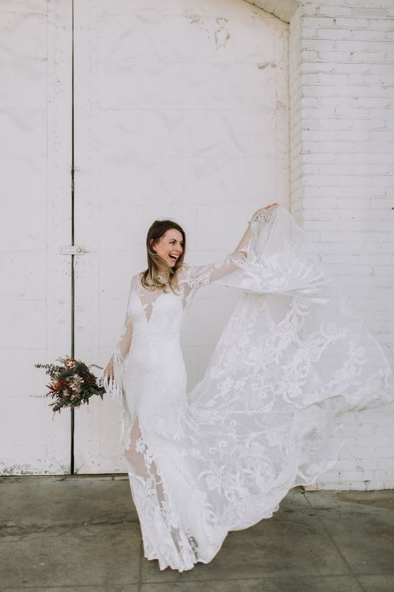 Adelia Lune gown with  long bell sleeves, fringe, lace appliques and a slip dress under