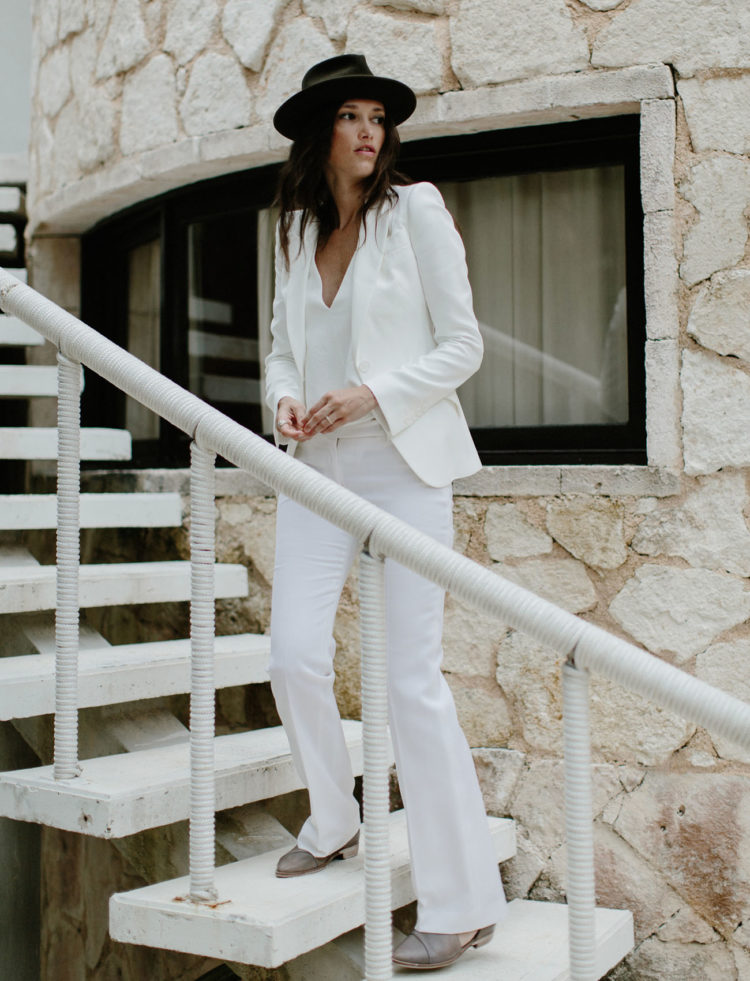 Katie wore a white pantsuit, a white top, leather booties and a hat