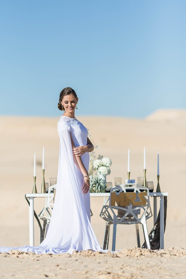 The bride was wearing a purely white wedding dress with an embellished neckline and a capelet