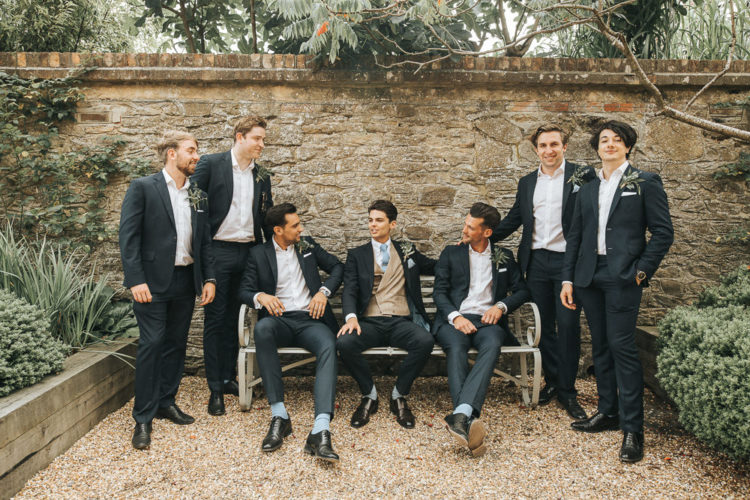 The groom was rocking a black suit with a beige vest