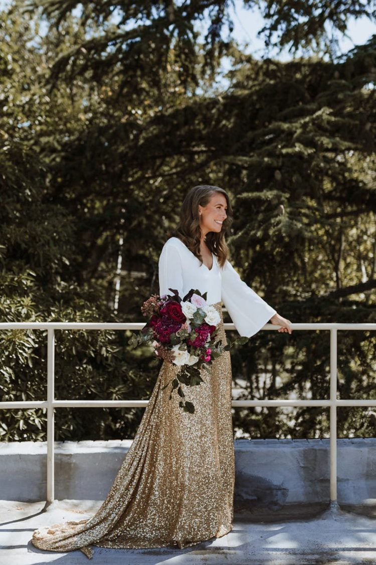 The second bride preferred a white top with bell sleeves and a gold glitter skirt with a train