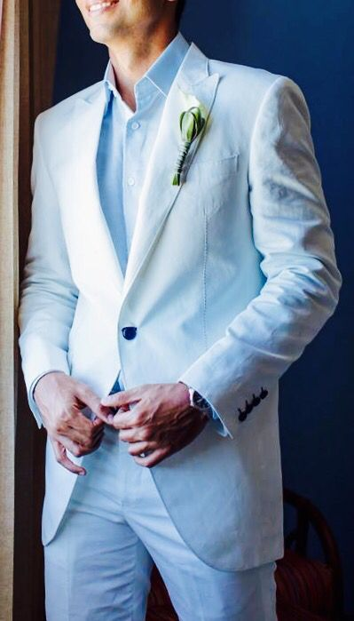 a beach groom's look with a white suit, a blue shirt and navy buttons and no tie