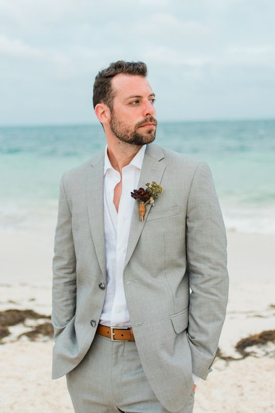 a grey suit, a white shirt, an amber belt for a relaxed yet stylish beach look