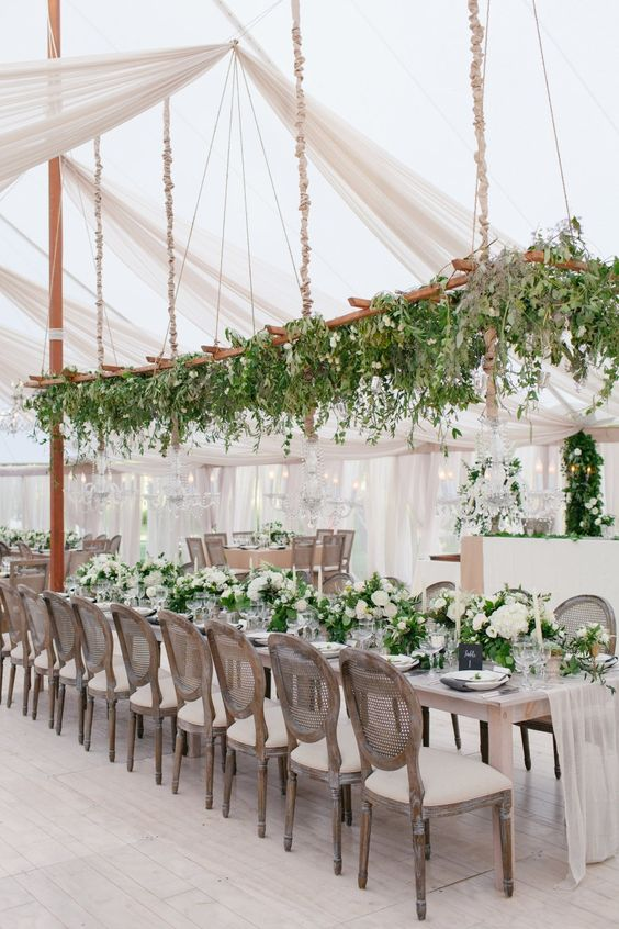 a hanging ladder over the reception decorated with lush greenery and pendant lights for a refreshing look
