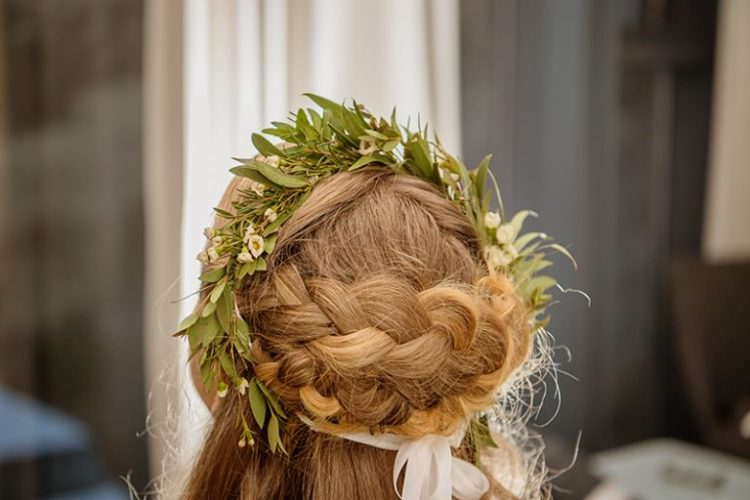 She was rockign a half updo with waves and braids on top and a greenery and flower crown