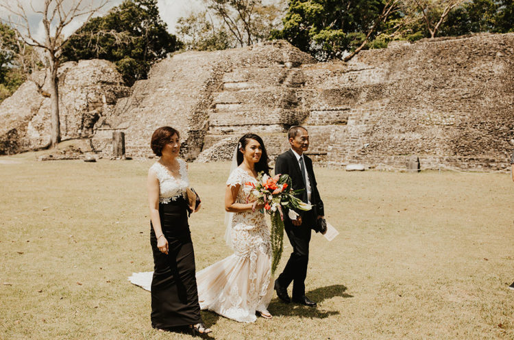 The bride was wearing a gorgeous mermaid lace wedding dress with an open back and a long tail