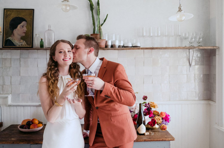 The bride was wearing a minimalist white sheath dress with a halter neckline