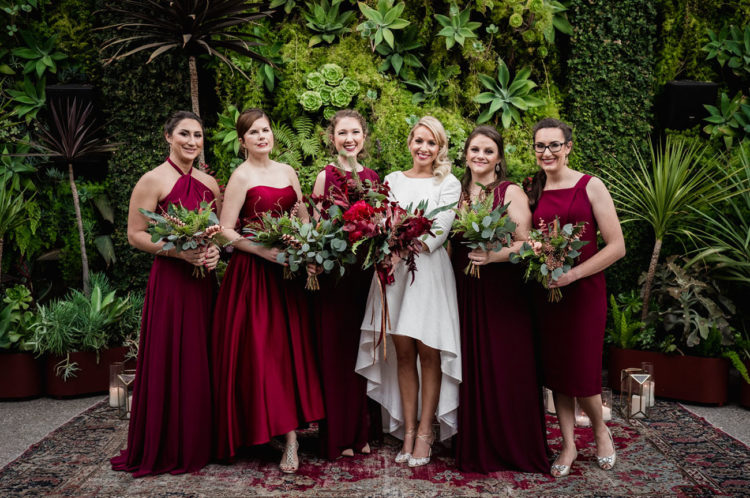 The bridesmaids were wearing mismatching burgundy dresses of their choice