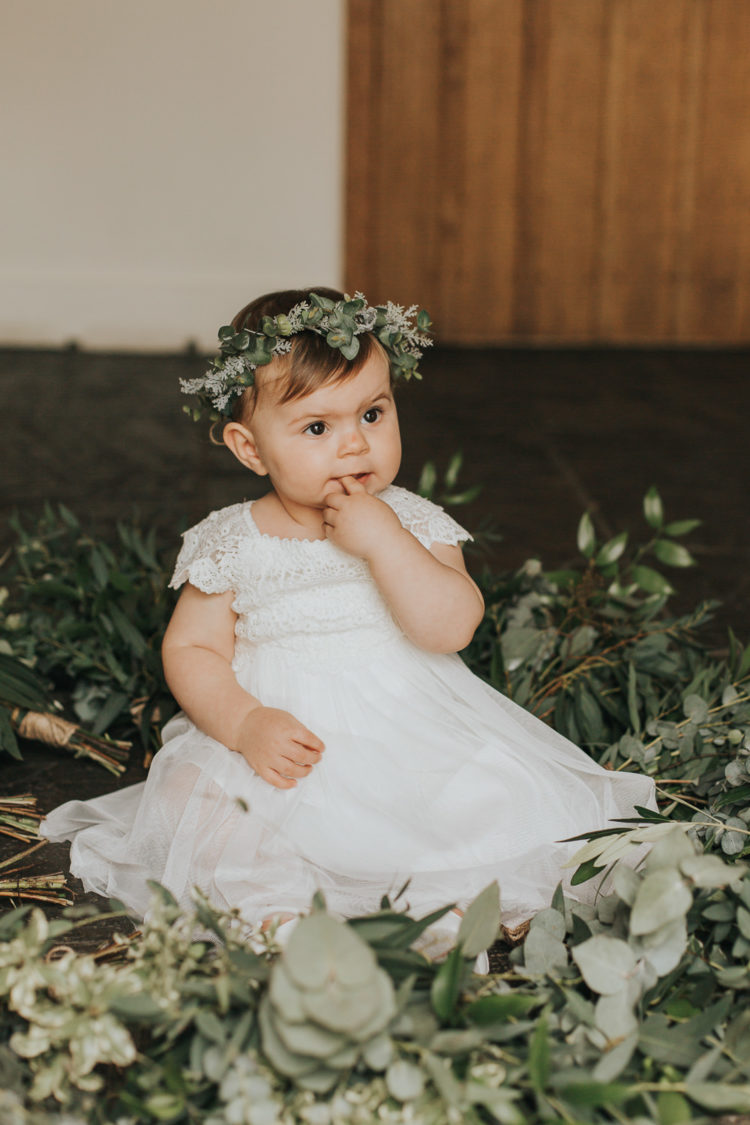 The daughter of the couple was dressed in a cute lace gown and a greenery crown