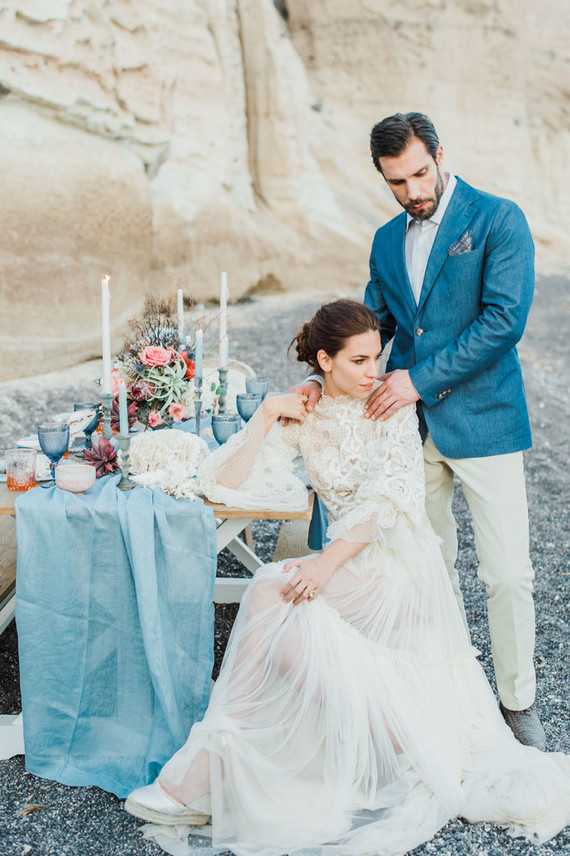 The groom was wearing a cream shirt and pants, a blue jacket and grey shoes