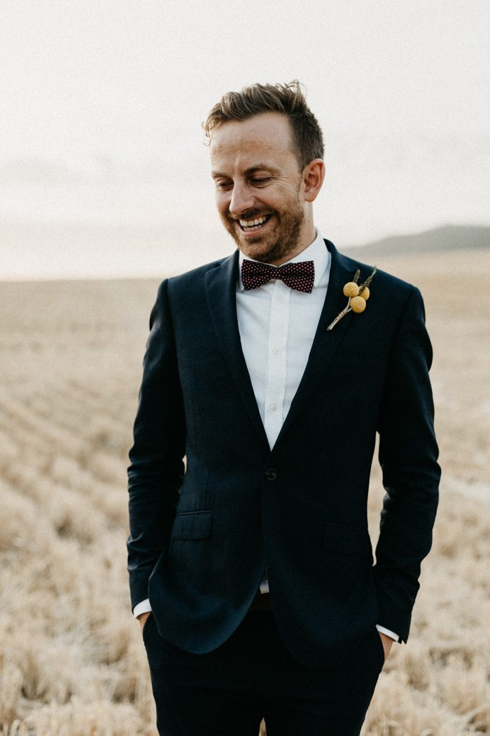 The groom was wearing a navy tuxedo with a polka dot bow tie and a billy ball boutonniere