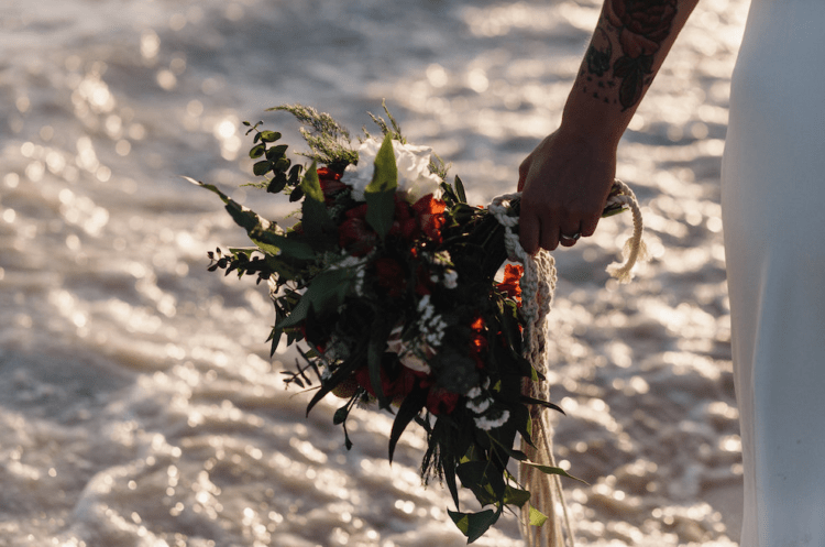 The wedding bouquet was done with white and red blooms plus textural greenery and a macrame wrap