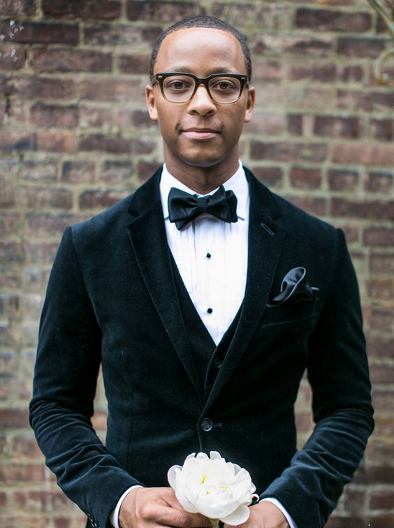 a black velvet tuxedo with a vest and a shirt with black buttons for a dapper look