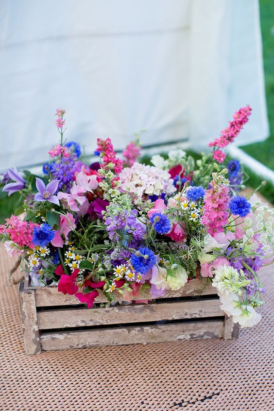 a crate with bright and vivacious blooms and greenery as a wedding decoration or centerpiece