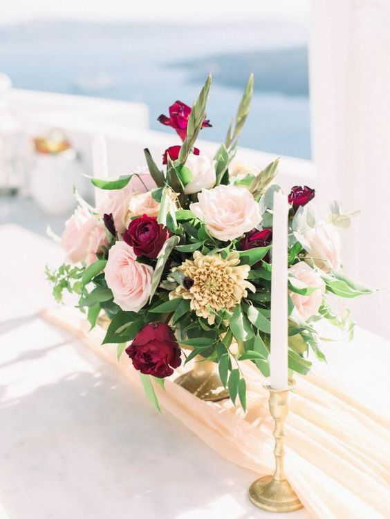 a gorgeous blush and burgundy wedding centerpieces with candles for a chic look