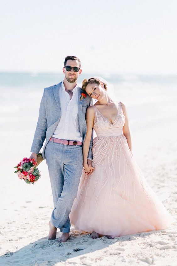 a grey suit, a pink belt to match the wedding dress for a serene look