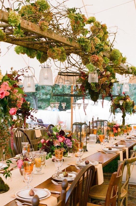 a ladder decorated with hydrangeas, branches and hanging lanterns with candles for a woodland wedding