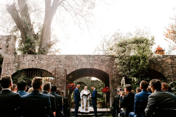 The ceremony space was an antique stone arch and there were two bright floral topiaries on each side