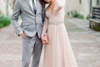 05 a blush wedding dress with a plunging neckline, long lace sleeves and an embellished sash