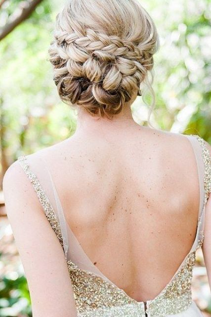 a braided and twisted low updo with some locks down gurantees a pictureperfect look all day
