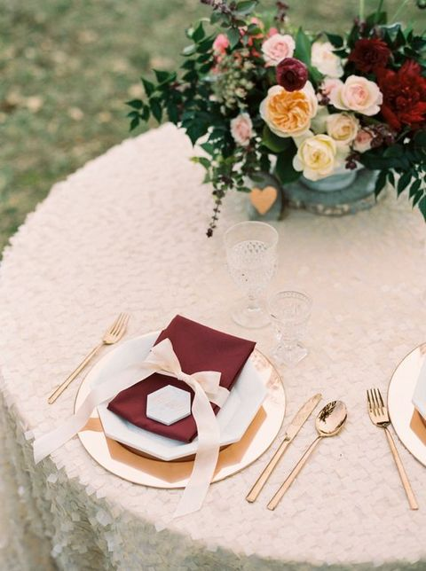 a glam table setting with touches of blush and burgundy plus a sequin tablecloth