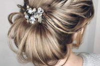 05 a messy and textural low chignon hairstyle with a light side braid and a large rhinestone and pearl hairpiece