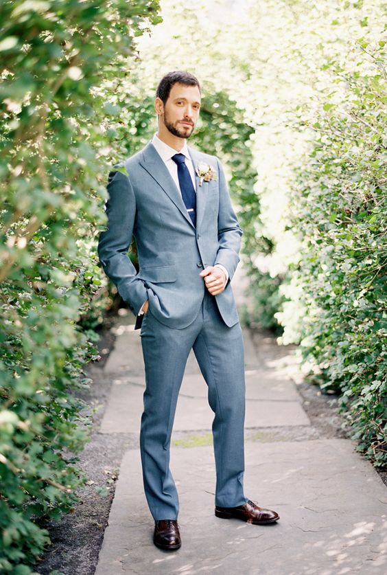 a modern grey suit, a navy tie, dark brown shoes for an effortlessly chic look