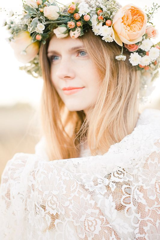 an oversized floral crown with peachy blooms and white smaller ones plus greenery for a bright late summer look
